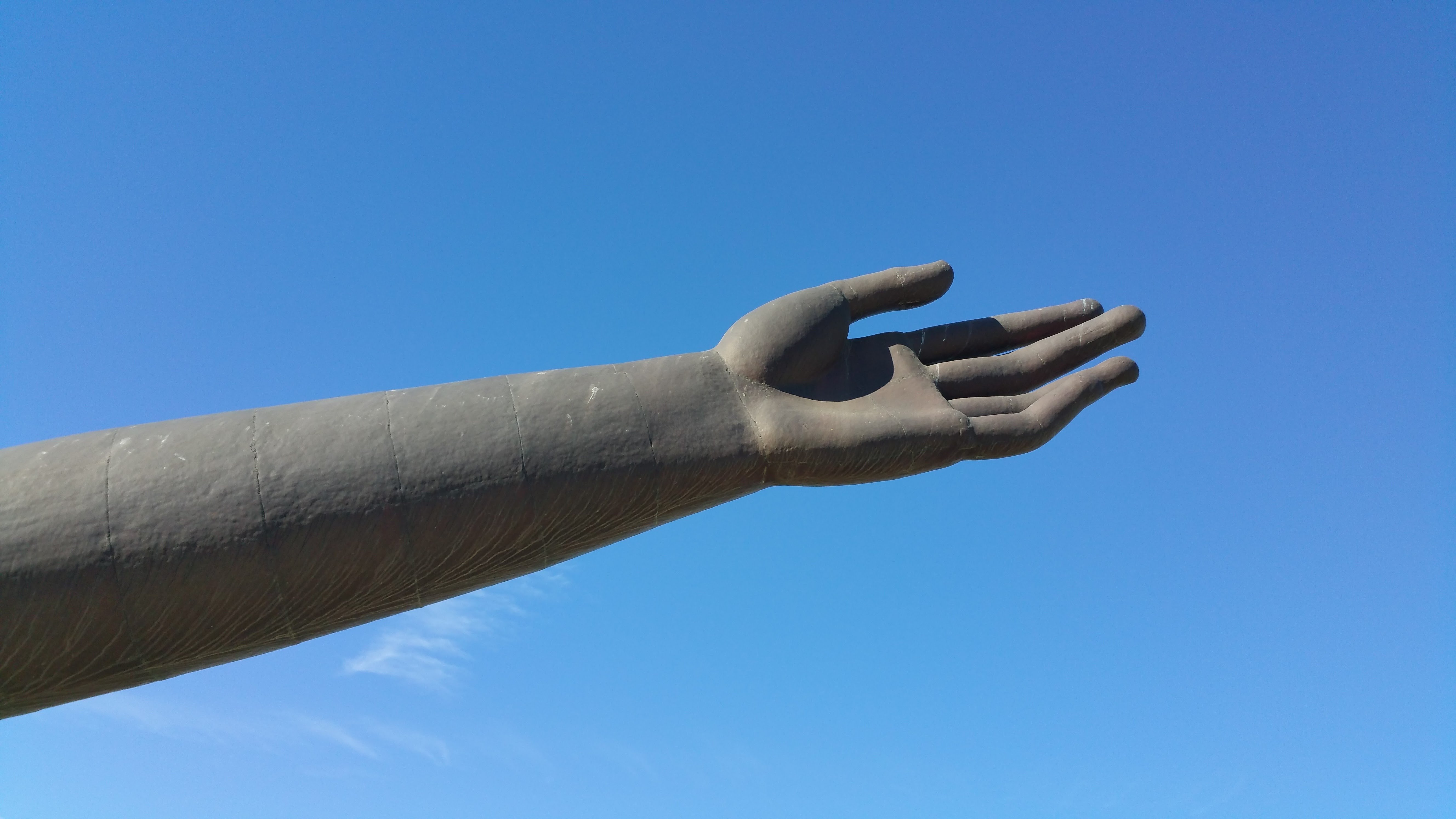 statue hand reaching into sky